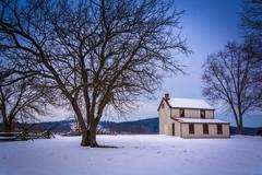 Small house and trees in a snow-covered field in gettysburg, pennsylvania. Stock Photos