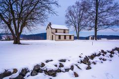 small house in a snow-covered field in gettysburg, pennsylvania. - stock photo