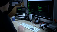 Stock Video Footage of Hacker programmer at work on computer with streaming code on screen