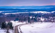 Stock Photo of view of road through snow-covered fields and distant mountains