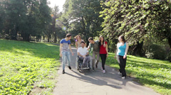 Invalid young man on the wheelchair having fun in the park with his friends - stock footage