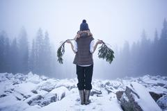 Caucasian woman holding tree branches on snow covered rocks Stock Photos