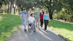Guy in wheelchair hangs out with his friends - stock footage