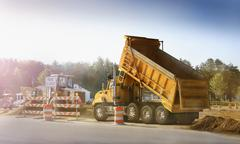 Dump truck dumping haul on site Stock Photos