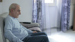old man getting up from the sofa feeling back pain - backache - stock footage