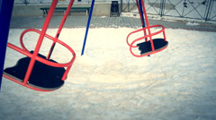 The empty swaying swings on the playground. Stock Footage