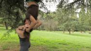 Stock Video Footage of woman runs to her boyfriend and kisses him, the man is on the tree upside down