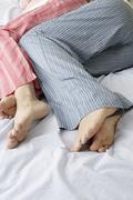 Caucasian pregnant lesbian couple laying on bed Stock Photos