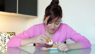 Stock Video Footage of young woman eating lots of sweets quickly