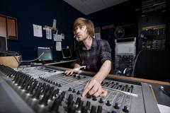 man using a sound mixing desk - stock photo