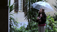 Stock Video Footage of nerdy man almost knocks his girl with umbrella