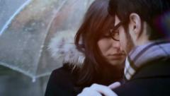 A man and a woman kissing under an umbrella in the rain - steadycam Stock Footage