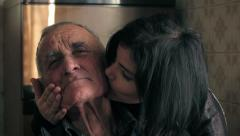 Beautiful woman caresses and kisses his grandfather looking at the camera Stock Footage