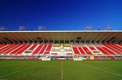 Amphitheater stadium with red seats under blue sky Stock Photos