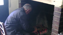 Old man cooks steaks on the grill in front of a fireplace Stock Footage