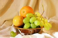 Stock Photo of grape, orange and plum in a vase