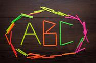 Stock Photo of abc letters formed with counting sticks over wooden background
