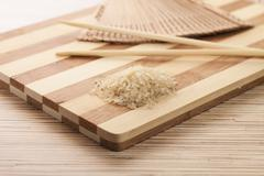 Raw rice ready to be cooked on the breadboard Stock Photos