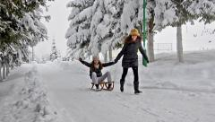 Beautiful joy teen pull sledge with happy sister on it having fun running Stock Footage
