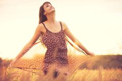 romantic model in sun dress in golden field at sunset - stock photo