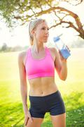athletic young woman runner drinking water - stock photo