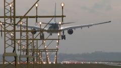 4K airplane landing on airstrip behind landing lights Stock Footage