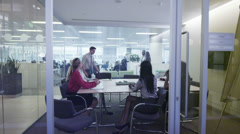 Attractive diverse business group in a team meeting in large busy city office. - stock footage