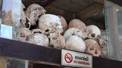 Tourist looks at skulls on shelf in memorial shrine at Killing Fields Stock Footage