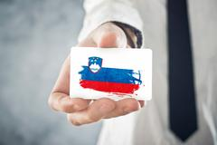 Stock Photo of slovenian businessman holding business card with slovenia flag