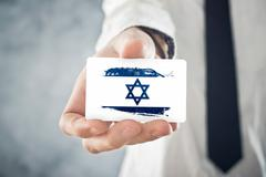 israelian businessman holding business card with israel flag - stock photo