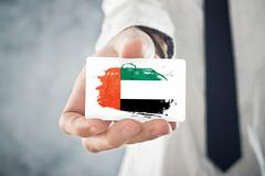 Businessman holding business card with united arab emirates flag Stock Photos
