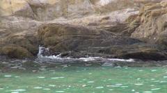 Calm sea water, emerald green ocean, rocky coast, crashing waves on cliff - stock footage
