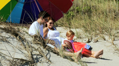 Caucasian Young Family Sun Parasol Playing Beach Toys Stock Footage