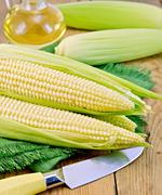 corncob with a knife and oil on board - stock photo