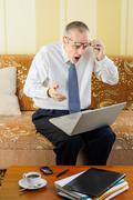 surprised senior businessman with computer - stock photo