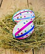 Easter eggs with ribbons and sequins in the hay Stock Photos