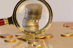 a stack of coins under a magnifying glass - stock photo
