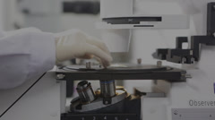 A researcher adjusts the slide on the specimen stage of a laboratory microscope Stock Footage