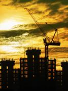silhouette of crane and building construction and sun set sky with copy space - stock photo