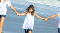 Three Young Caucasian Sisters Outdoors Linked Hands Beach - stock footage