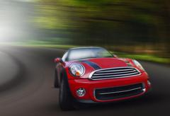 Stock Photo of red passenger car driving on asphalt road in curve ways of mountain high ways