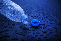 Open cap of empty platic bottle lying on dark wet floor Stock Photos
