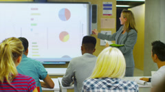 Attractive young teacher in class, explaining a subject to her students.  - stock footage