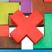 cross shaped piece on wood puzzle close up - stock photo