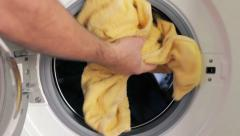 Placing dirty clothes in a washing machine Stock Footage