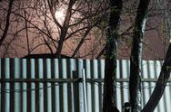 Stock Photo of night photography. moon over the fence and trees