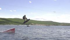 SLOW MOTION: Wakeboarder jumping the kicker in wake park Stock Footage