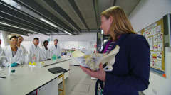 Female teacher teaching group of university students in a science class Stock Footage