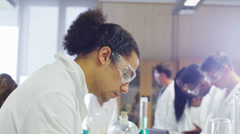 Female teacher teaching group of university students in a science class - stock footage