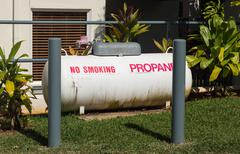 large propane tank in landscaped garden - stock photo